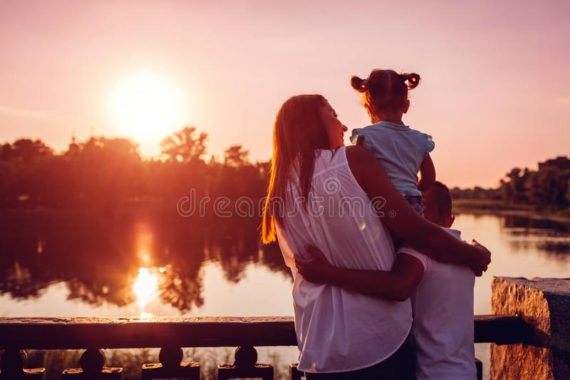 Happy family spending time outdoors hugging and enjoying the view of river at sunset. Mother with two kids. stock images