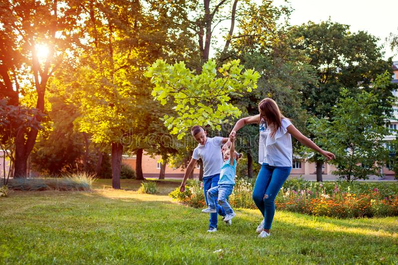 Happy family spending time outdoors playing in park. Mom having fun with two kids. Family values royalty free stock photo