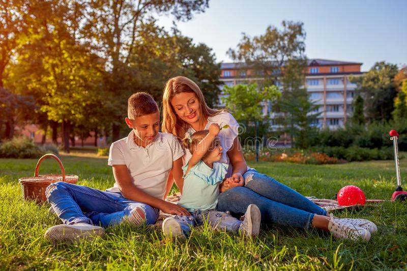 Happy family spending time outdoors sittting on grass in park. Mom with two children smiling. Mother`s day royalty free stock photo
