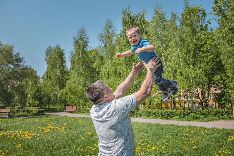 Happy joyful father having fun throws up in the air child. summer Sunny day in the city. father`s day. royalty free stock photo