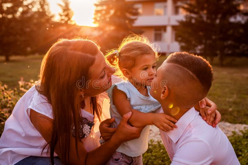 Happy family spending time outdoors walking in park. Mother and her son hugging little toddler girl and talking. Happy family spending time outdoors walking in stock image