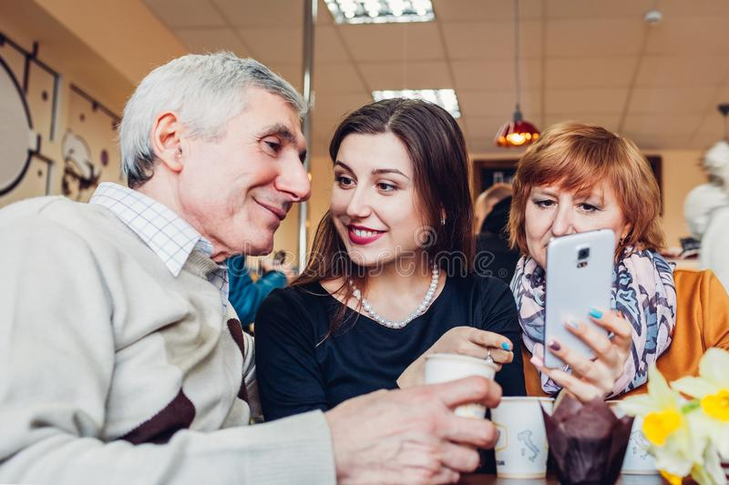 Happy family spending time together. Senoir family couple with adult daughter using a smartphone in the cafe. royalty free stock photo