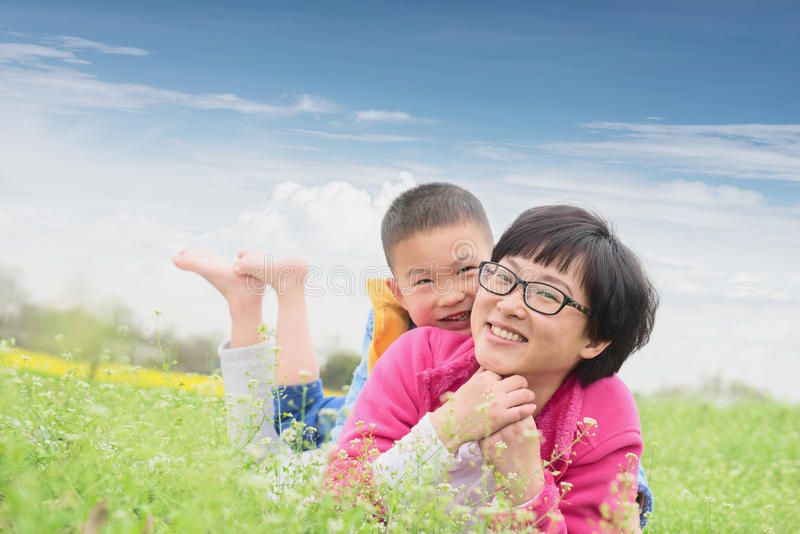 Happy family in spring. Chinese happy family lying on lawn in spring with blue sky background stock photo