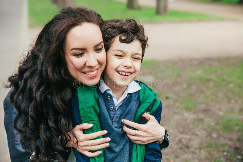 Happy family in spring park. Young mother and her son spending time outdoor on a summer day stock images