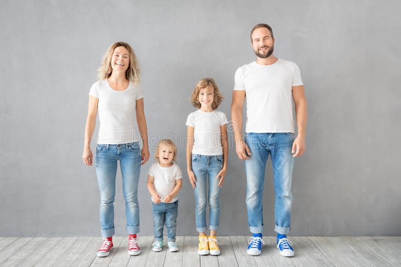 Happy family standing against grey background royalty free stock photography