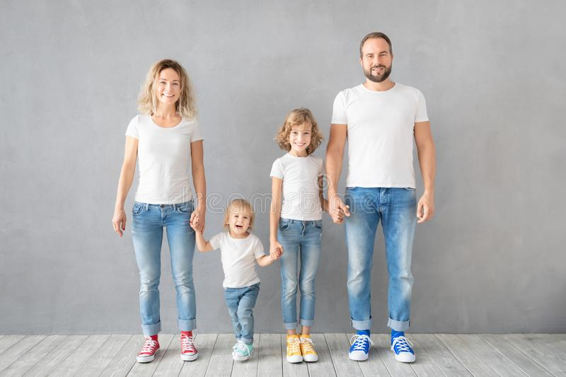 Happy family standing against grey background stock photo