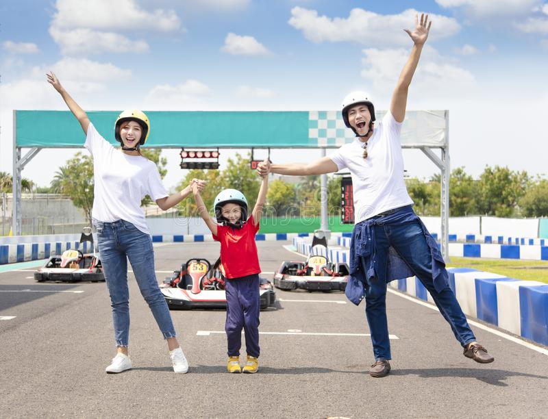 Happy family standing on the go kart race track stock photo