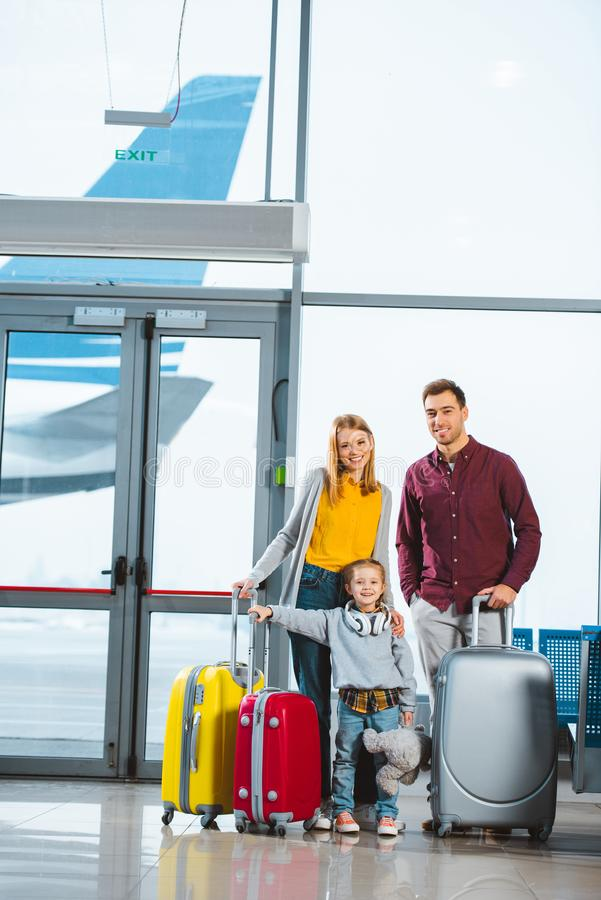 Happy family standing near baggage and smiling in stock photo