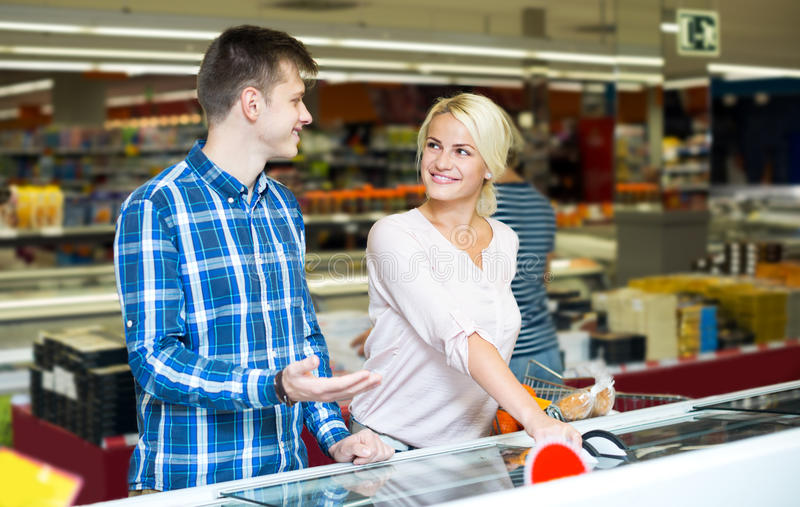 Happy family standing near display with frozen food stock photo