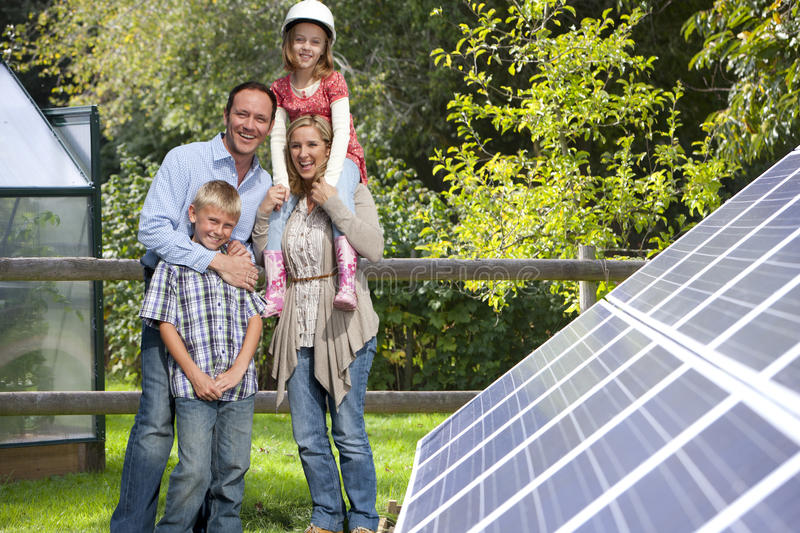 Happy family standing near large solar panels royalty free stock images