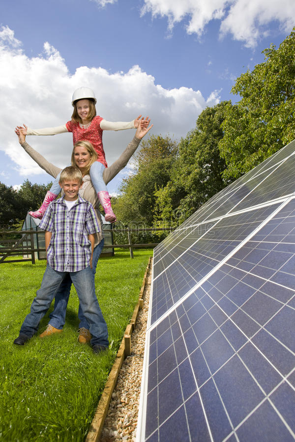Happy family standing together near large solar panels stock photo