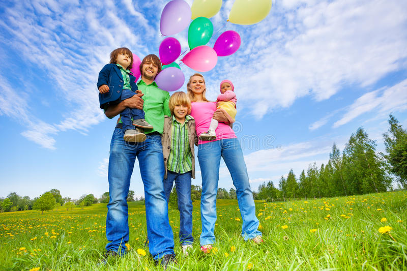 Happy family stands with balloons in park. In summer stock photos