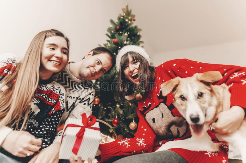 Happy family in stylish sweaters and cute funny dog exchanging g. Ifts at christmas tree with lights. emotional moments. merry christmas and happy new year stock images