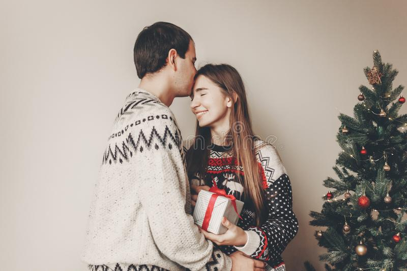 Happy family in stylish sweaters exchanging gifts in festive room with christmas tree and lights. emotional moments. merry christ. Mas and happy new year concept stock image