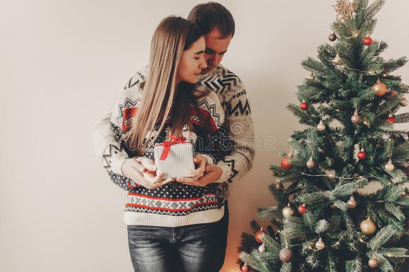 Happy family in stylish sweaters exchanging gifts in festive room with christmas tree and lights. emotional moments. merry christ. Mas and happy new year concept royalty free stock images