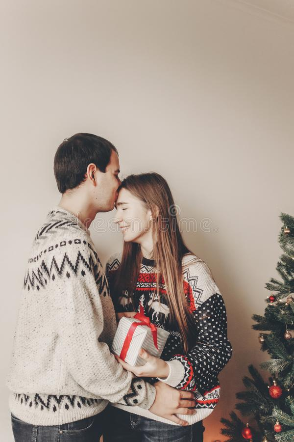 Happy family in stylish sweaters exchanging gifts in festive room with christmas tree and lights. emotional moments. merry christ. Mas and happy new year concept stock photos