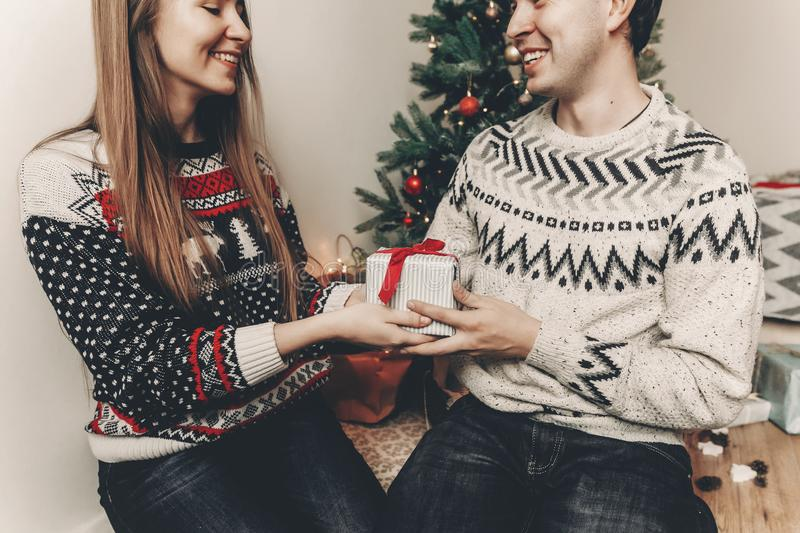 Happy family in stylish sweaters exchanging gifts in festive room with christmas tree and lights. emotional moments. merry christ. Mas and happy new year concept royalty free stock photography