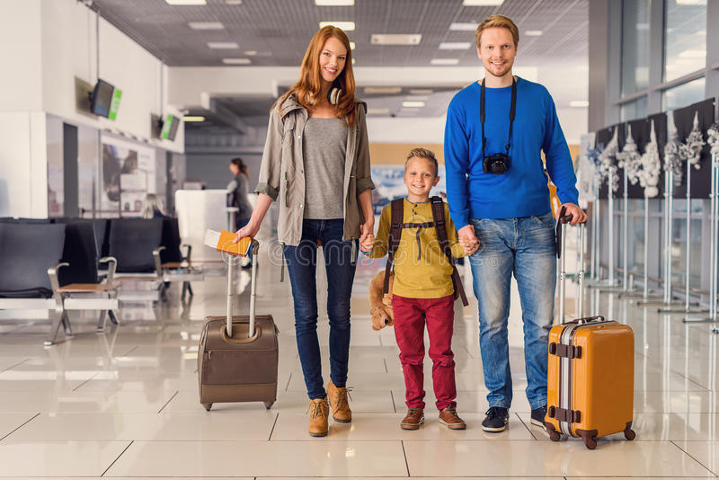 Happy family with suitcases in airport royalty free stock photos