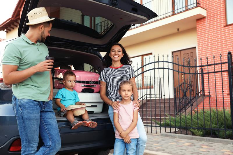Happy family with suitcases near car stock photos