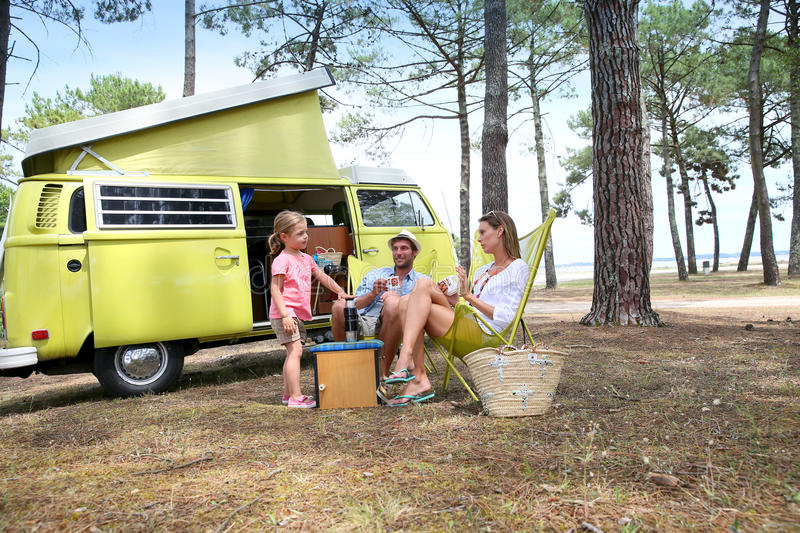 Happy family on summer holidays camping. Happy family relaxing by camper van in summer stock photo