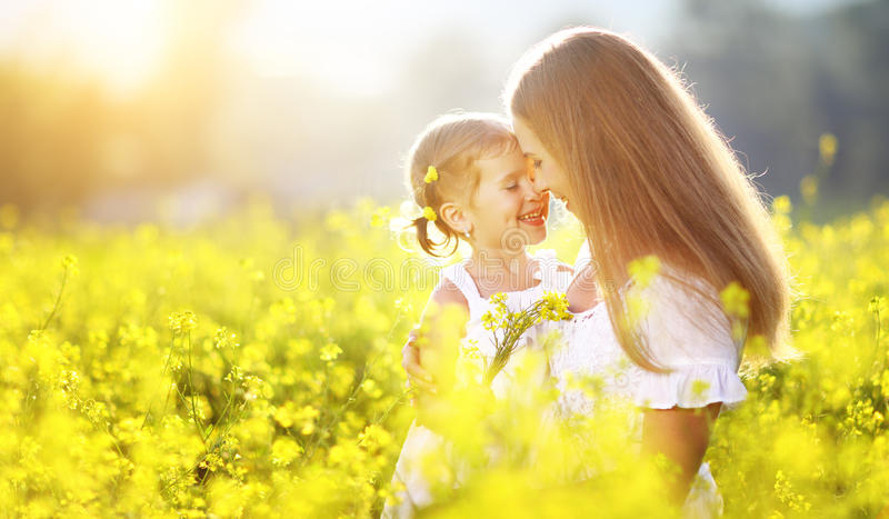 Happy family on summer. little girl child daughter hugging and k. Happy family on a summer meadow. little girl child daughter hugging and kissing mother royalty free stock image