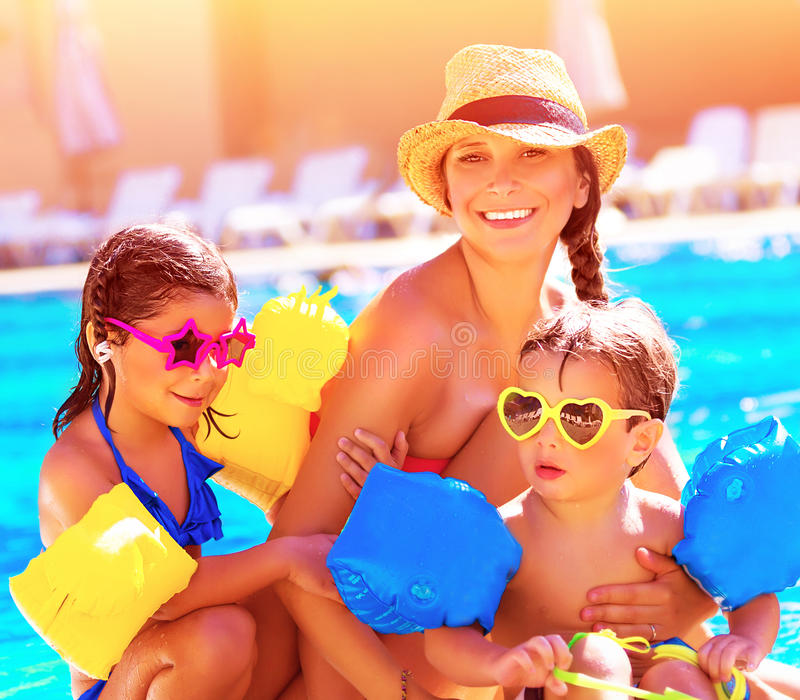 Happy family in summer vacation. Young mother with two cute kids having fun near swimming pool on beach resort, love and friendship concept royalty free stock photography