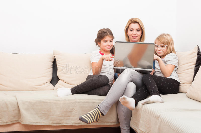 Happy family surfing or browsing internet together. Using laptop relaxed on the sofa or couch stock images
