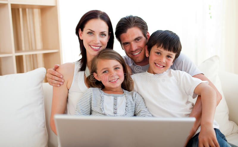 Happy family surfing the internet. On the sofa royalty free stock photos