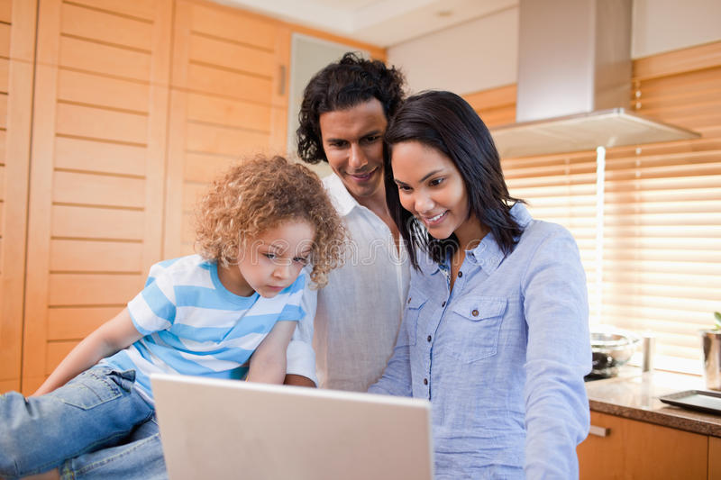 Happy family surfing the internet in the kitchen together. Happy young family surfing the internet in the kitchen together royalty free stock images