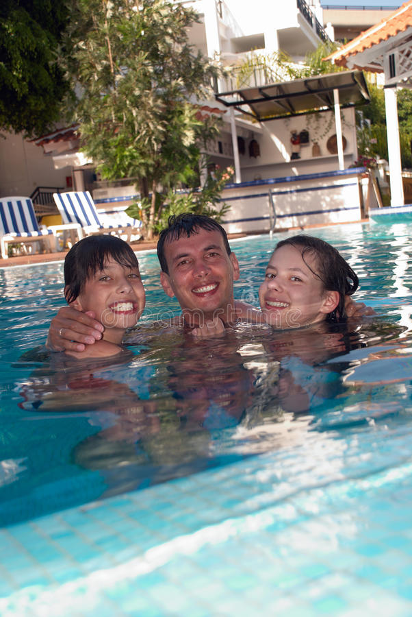 Happy family in swimming pool. Happy family in the swimming pool of luxury hotel royalty free stock photography