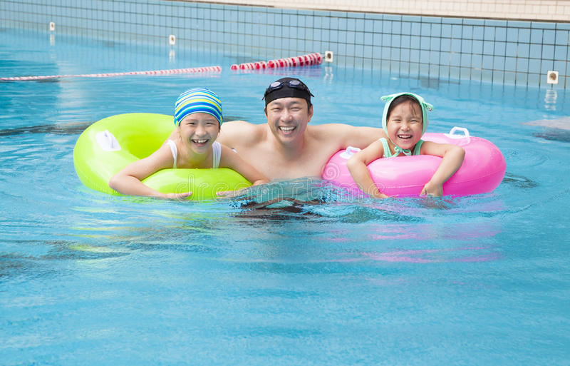 Happy family in the swimming pool. Happy asian family in the swimming pool royalty free stock photo