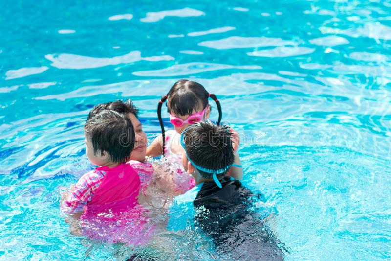 Happy family in swimming pool. Father and his children. royalty free stock photo