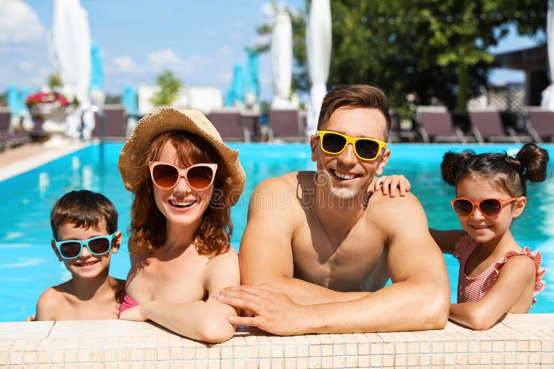 Happy family in swimming pool. At resort royalty free stock photo