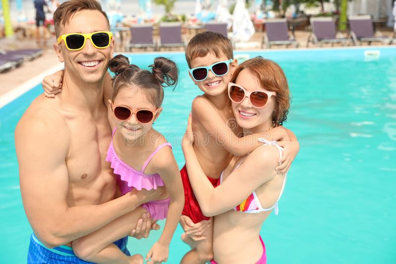 Happy family in swimming pool. At resort stock image