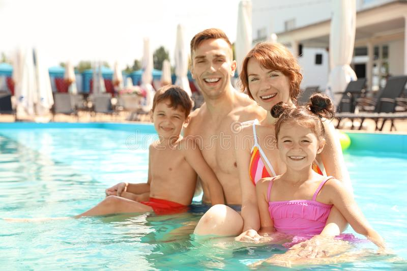 Happy family in swimming pool. At resort royalty free stock image