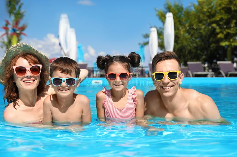 Happy family in swimming pool. At resort stock photos