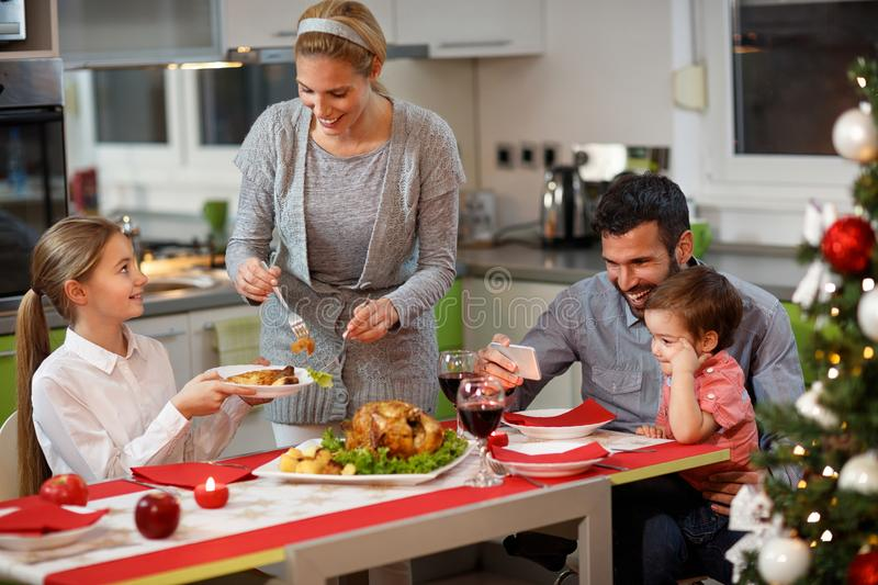 Happy family at the table having gala Christmas dinner royalty free stock image