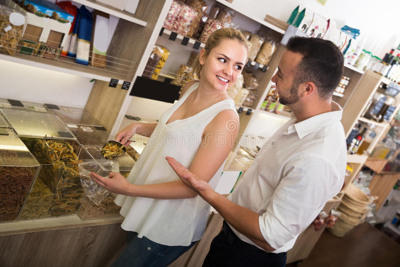 Happy family taking with scoop pasta. Happy young family taking with scoop pasta sold by weight in organic shop royalty free stock photos