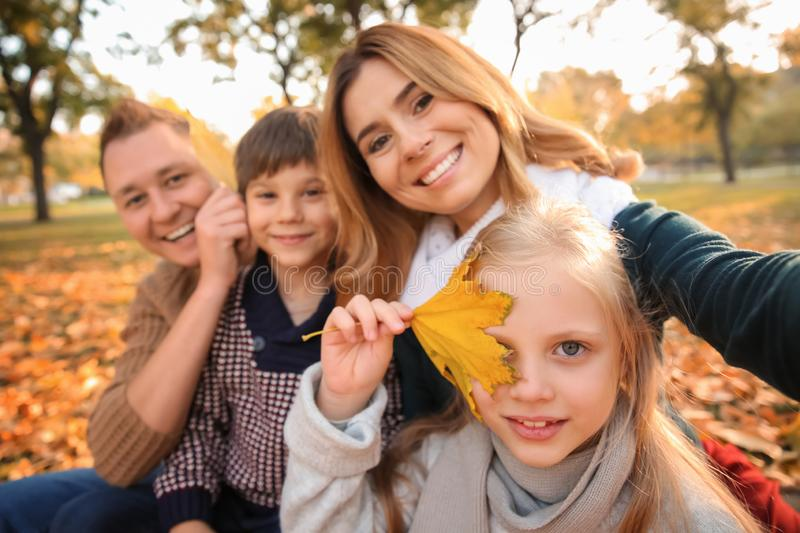 Happy family taking selfie in autumn park stock photography