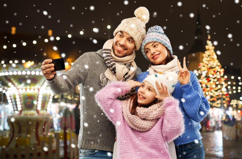 Happy family taking selfie at christmas market stock photos