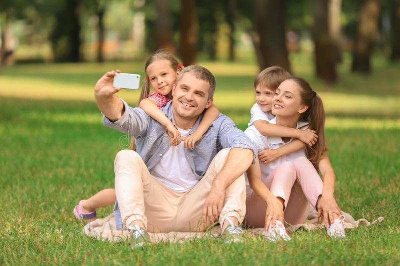 Happy family taking selfie in green park royalty free stock photos