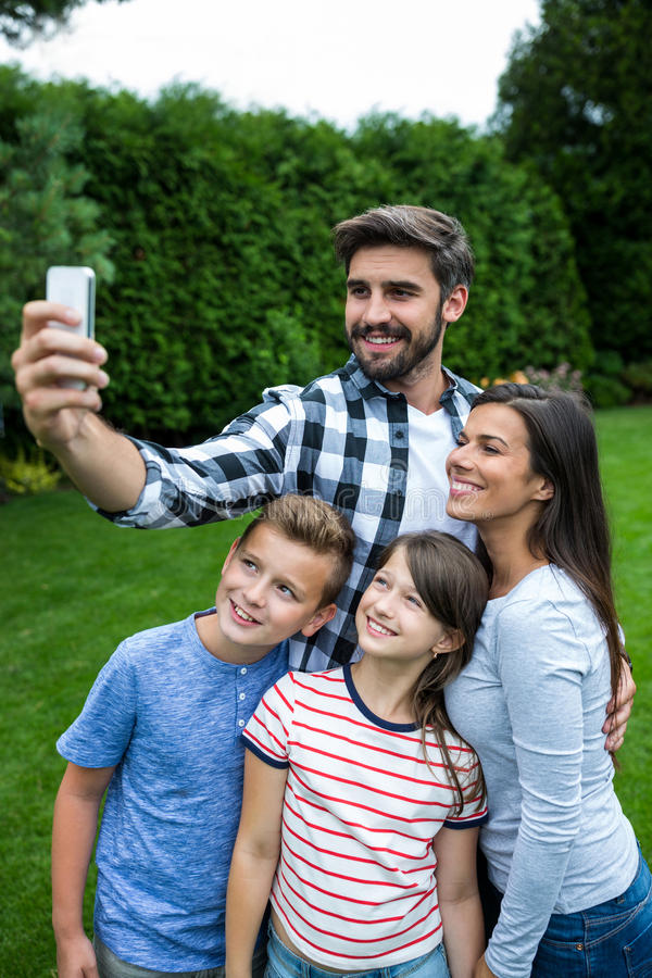 Happy family taking a selfie from mobile phone in park. On a sunny day royalty free stock image