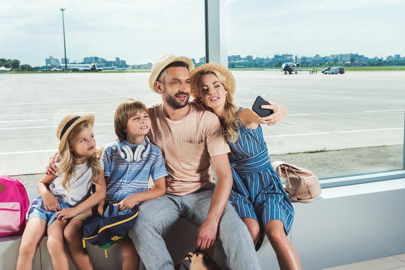 Happy family taking selfie in airport royalty free stock photo