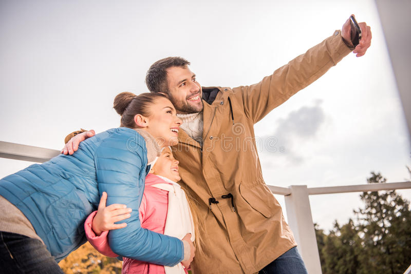 Happy family taking selfie. Happy smiling family hugging and taking selfie at autumn day stock photos