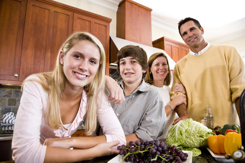 Happy family with teenage children in kitchen stock images