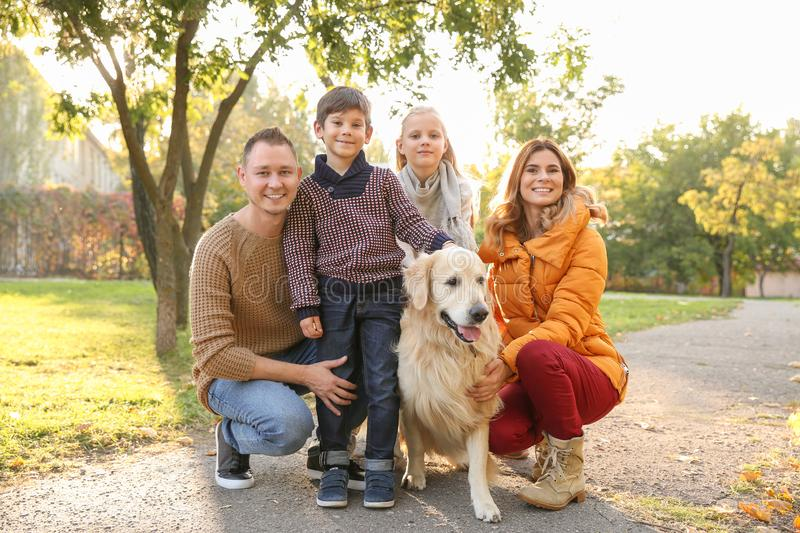 Happy family with their dog in autumn park royalty free stock photo