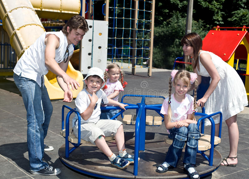 Happy family and three children in park. stock photo