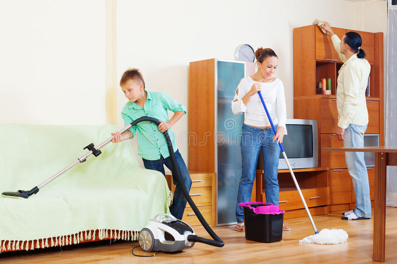 Happy family of three cleaning in living room stock photography