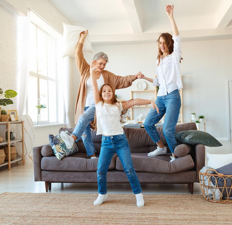 Family three generations  grandmother, mother and child dancing, jumping and laugh at home. Happy family three generations   grandmother, mother and child royalty free stock images