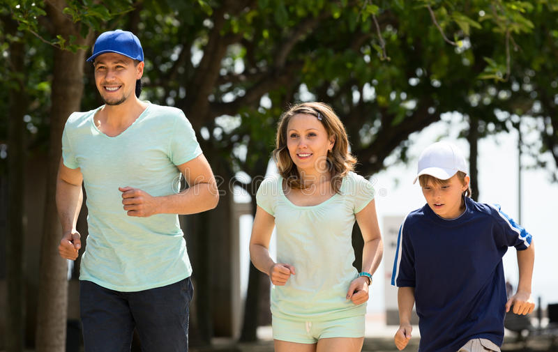 Happy family of three jogging royalty free stock photography